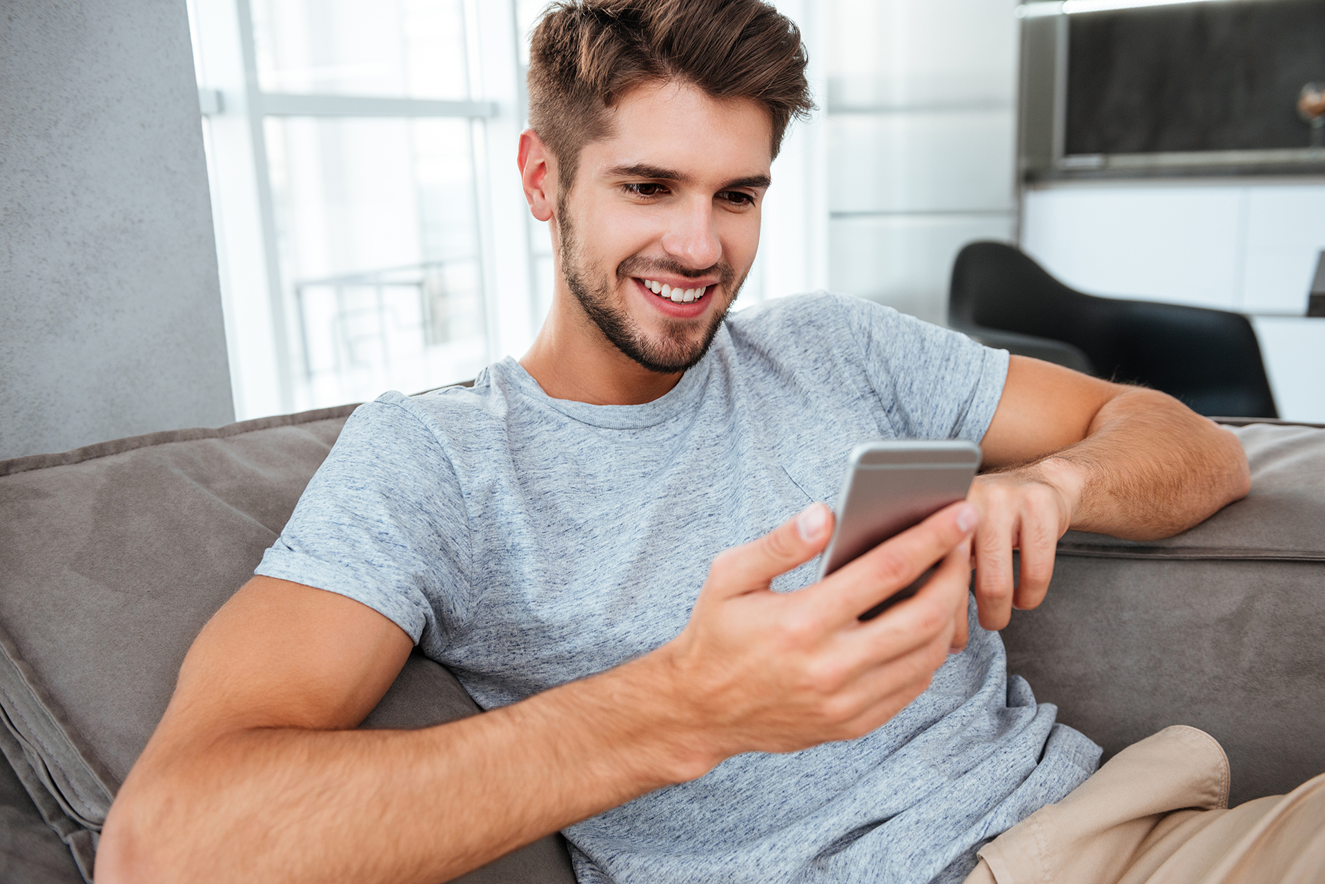 Photo of cheerful young man lies on sofa and chatting. Looking at smartphone.