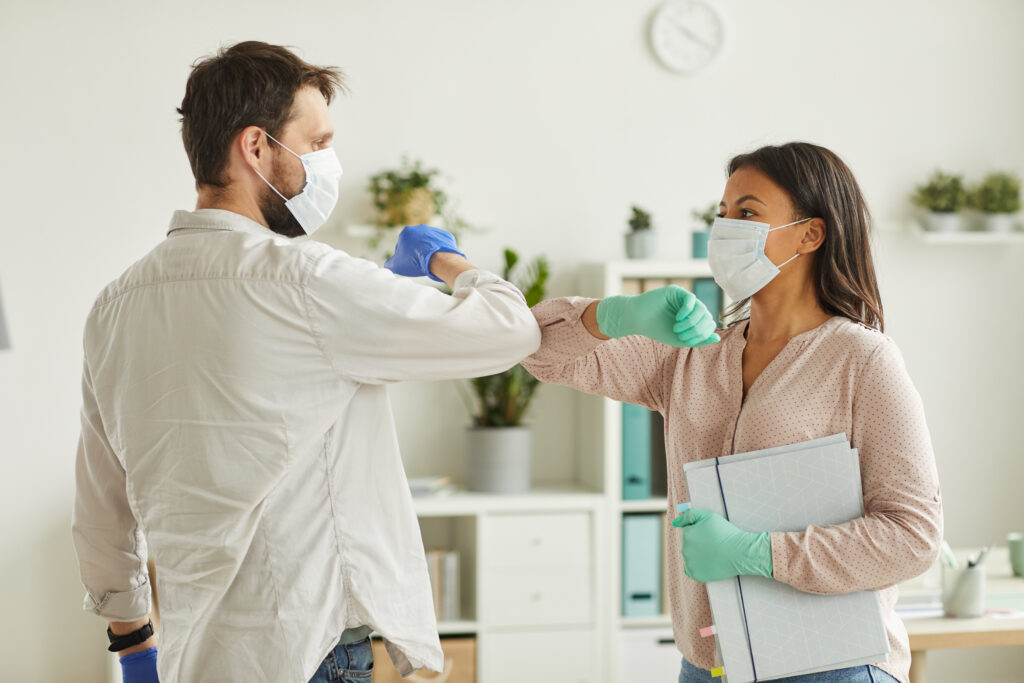 Waist up portrait of two colleagues wearing face masks bumping elbows while greeting each other at work in office